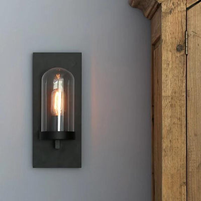 Black wall light with a glass dome over the bulb