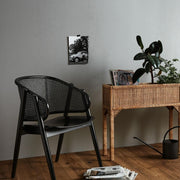 Black wicker curved chairs with a geometric pattern back