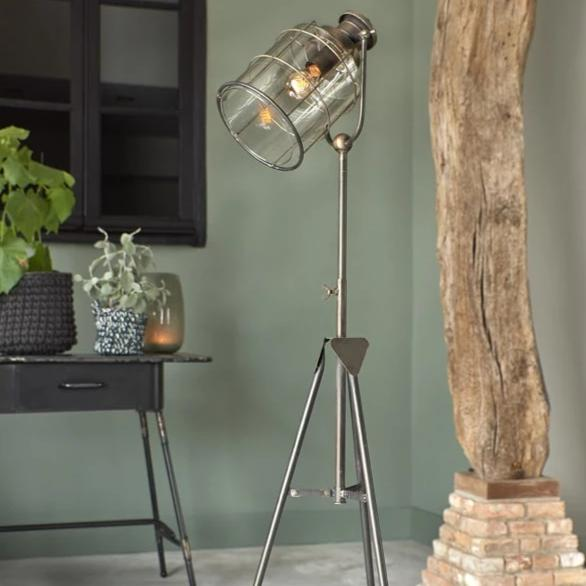 Tripod base industrial style brass floor lamp with a glass shade over the bulb
