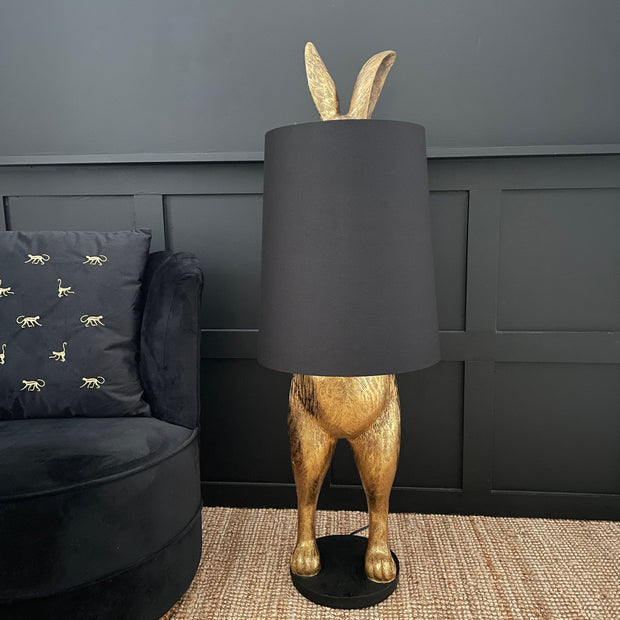 Gold bunny rabbit table and floor lamp which is hiding behind a black lampshade