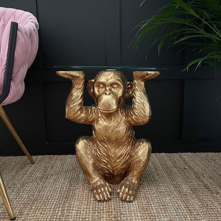 Gold monkey side table holding a circular glass top