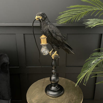 Black crow on a stick table lamp with a bulb in it's mouth