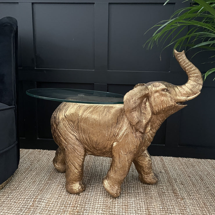 Gold elephant side table with it's trunk up in the air