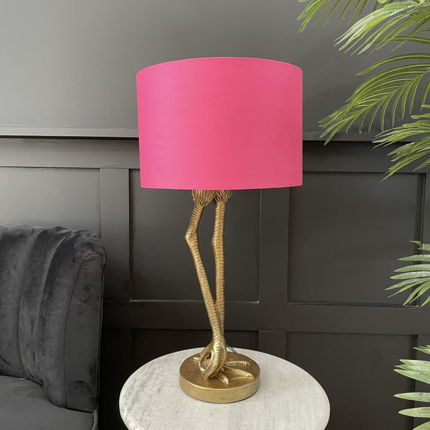 Gold flamingo leg table lamp with a bright pink round lamp shade