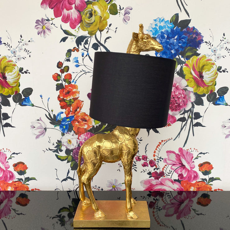Gold giraffe table lamp with the lampshade over the neck