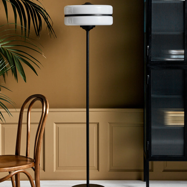 Opal glass floor lamp waisted by a black iron band