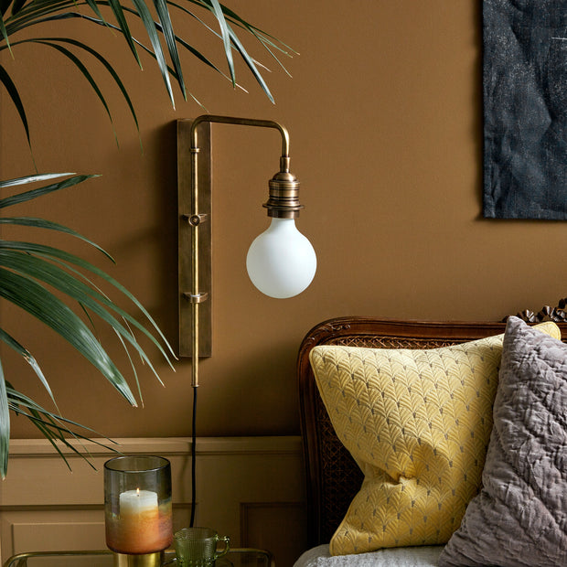 Brass plated iron wall light with a black cord