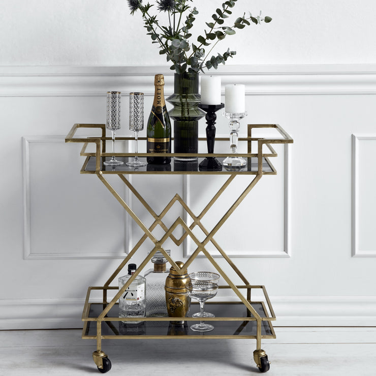 Gold drinks trolley with two dark shelves and wheels
