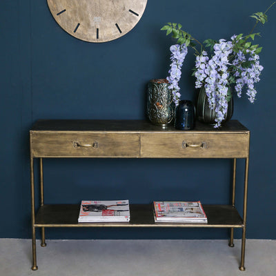Gold metal console table with two drawers and a bottom shelf