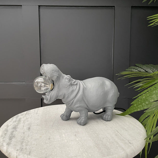 Grey hippo table lamp with the bulb in it's mouth