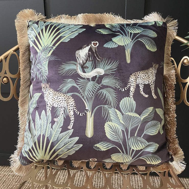 Black jungle cushion with green plants & wild animals, as well as gold fringed edge