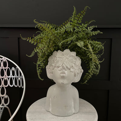 Large grey planter of a person pouting with a flower head