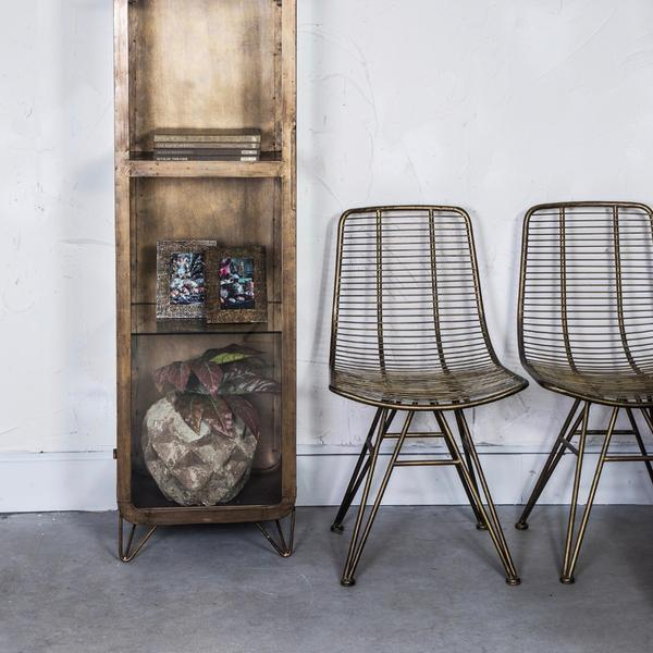 Two brass metal dining chairs with linear finish next to a brass cabinet