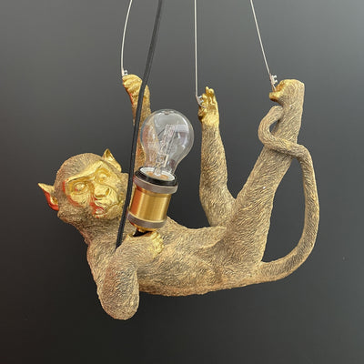 Gold monkey ceiling light on it's back hanging from wire