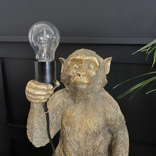 Gold table lamp of a monkey standing holding a light bulb