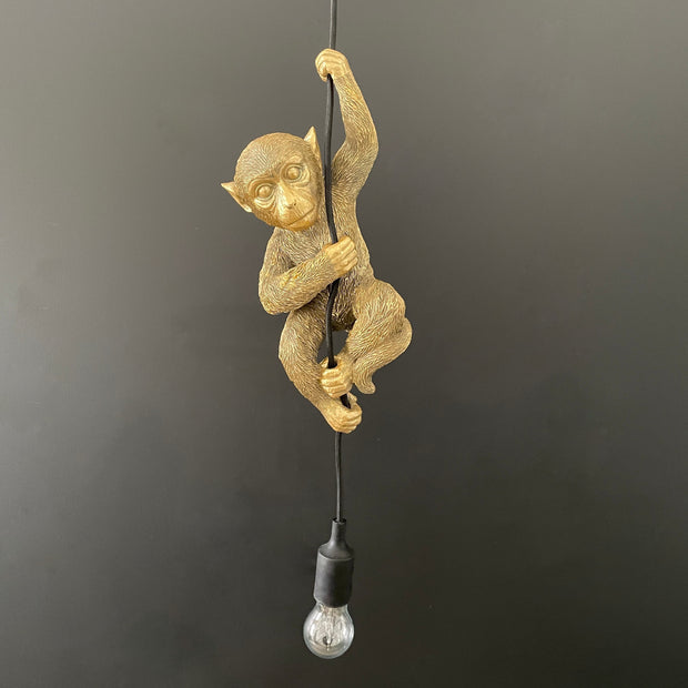 Hanging ceiling light with a gold monkey hanging from it