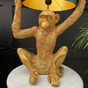 Gold sitting monkey table lamp holding the stand with a black lamp shade