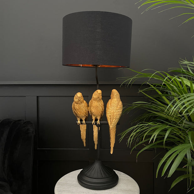 3 gold parrots sat on a black branch table lamp with a black shade