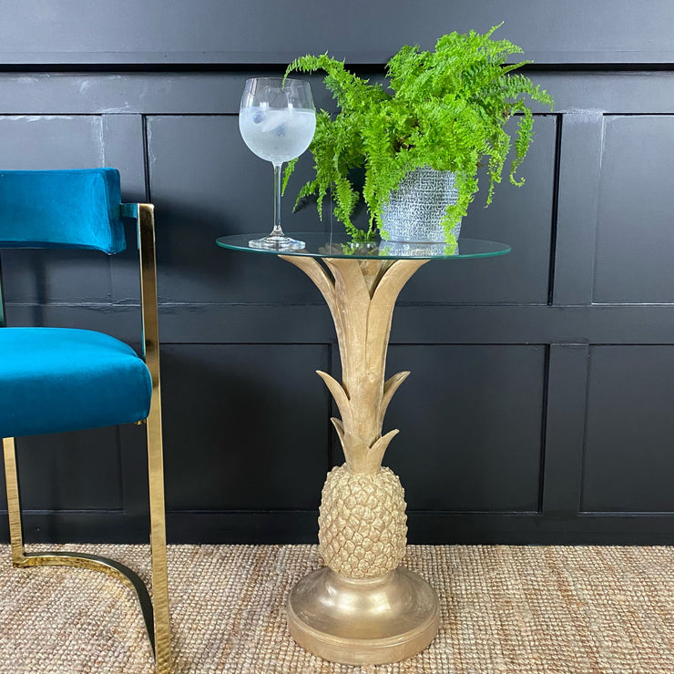 Gold pineapple side table with a round glass top