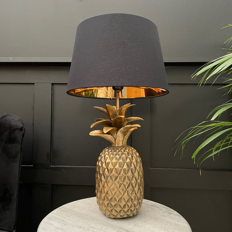 Gold pineapple table lamp with a black shade with a gold metallic interior