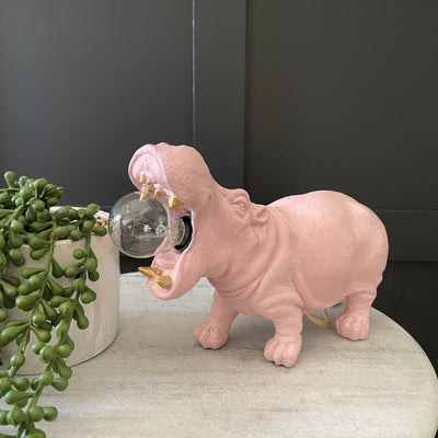 Pink hippo table lamp with a bulb in it's mouth