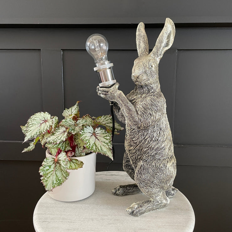 Silver rabbit table lamp holding a bulb