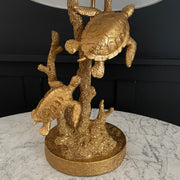 Gold turtle table lamp with a white lampshade