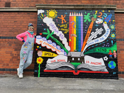 Colourful artist Anna Hughes of Anya's studio with rainbow exterior mural