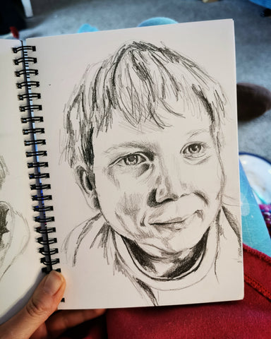 Pencil drawing of a child's face portrait, by Anna Hughes, Anya's Studio