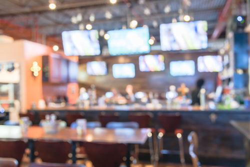 Blurred image of sport and oyster bar with TV, classic counter, tables and chairs in Houston, Texas, US. Bar Happy Hour, dine in abstract background. Night club and grill bar concept.