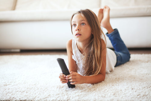 child watching tv laying down on a white carpet