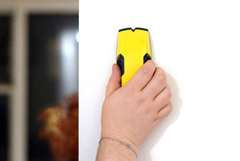 person using stud finder wall