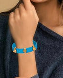 Blue and Gold Leather Spike Bracelet with Agate Stones in hands