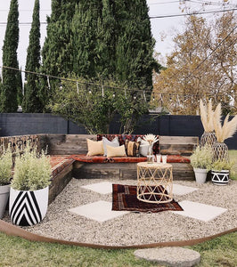 white and black diamond pattern planter in outdoor bohemian sitting space