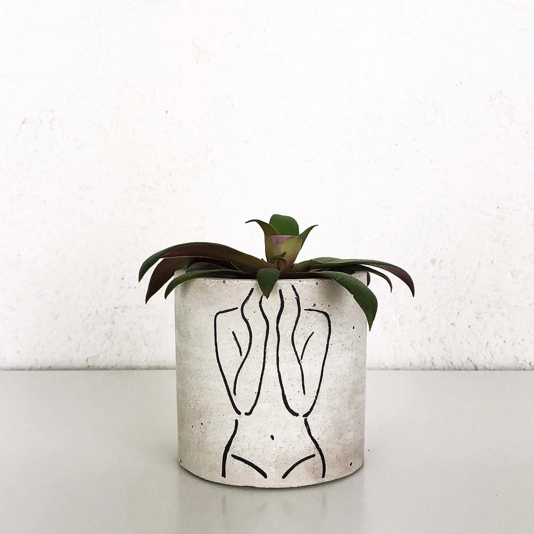 small concrete planter with female torso artwork