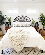 black and white diamond pattern plant pots on beside tables with black rattan headboard