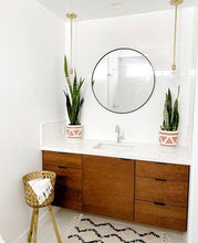 two terracotta aztec bohemian planters on counter top in powder room