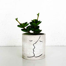 concrete planter pot with an outline of two portraits kissing