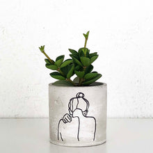 concrete planter with outline of the back of a lady with her hair in a bun