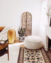 aztec planter in living room with large pouf