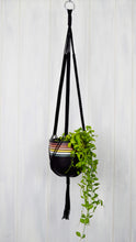 Black hand painted retro plant pot hanging from a black plant hanger