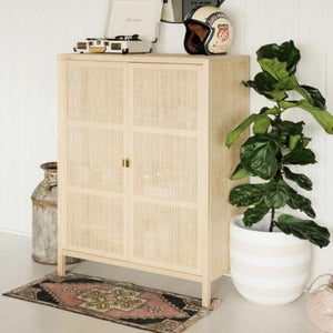 white and tan rugby striped planter pot with a fiddle leaf fig next to a white washed cane credenza