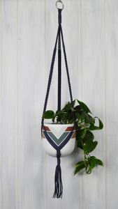 Hand painted Marrakesh Common House Studio planter pot hanging in a Navy plant hanger