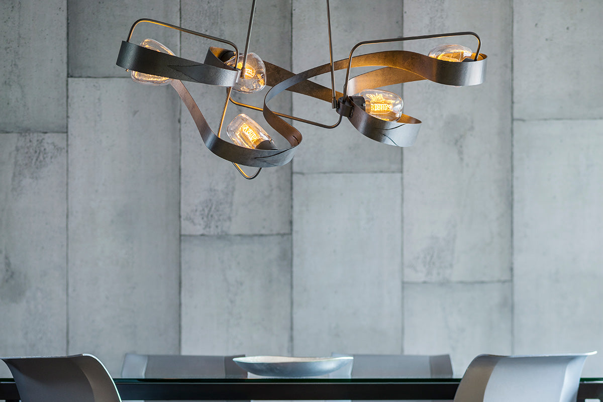 Hubbardton Forge's Graffiti Pendant in Dark Smoke is an eye-catching statement chandelier for this dining room.
