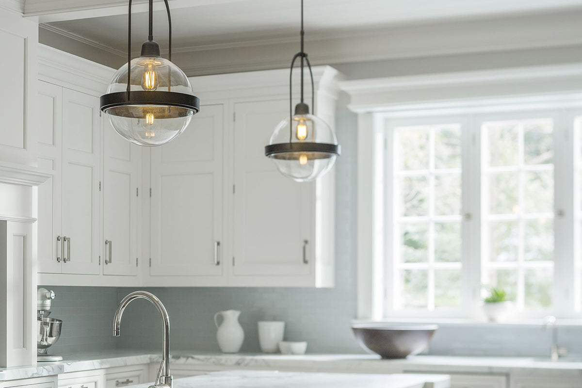 The Atlas Pendant by Hubbardton Forge adds industrial style to this kitchen.