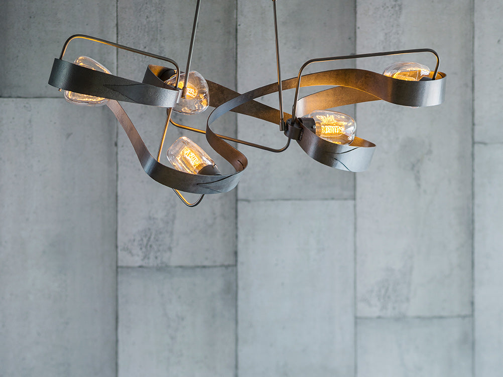 Hubbardton Forge's Graffiti Chandelier features heavy metalwork, blown glass, and vintage Edison bulbs.
