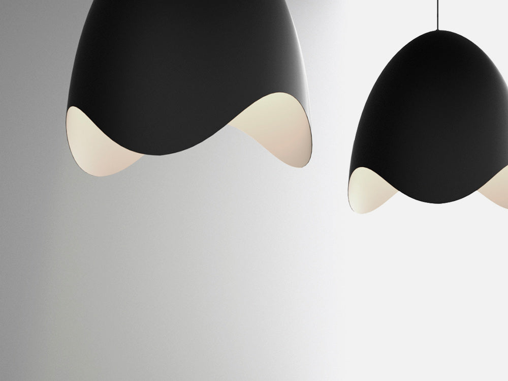 Sonneman's clean and modern Waveforms pendants have a black exterior and a white or apricot finish inside.