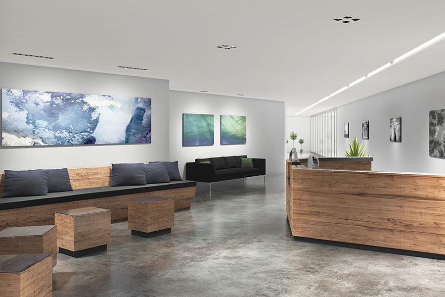 A modern office space that uses recessed lights for task lighting. The recessed lights highlight artwork on the walls.