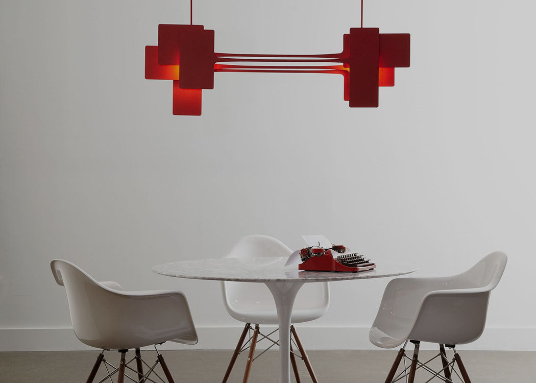 Hubbardton Forge's Stretch Pendant in Red brings a pop of color to this modern dining space.