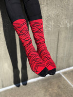 Red sock black stripe sitting on concrete